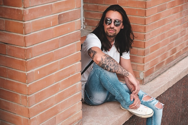 Séduisante jeune homme portant des lunettes de soleil avec des tatouages