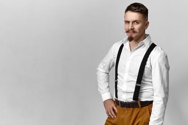 Séduisante jeune homme de race blanche viril avec moustache de guidon et barbiche vêtue de vêtements à la mode