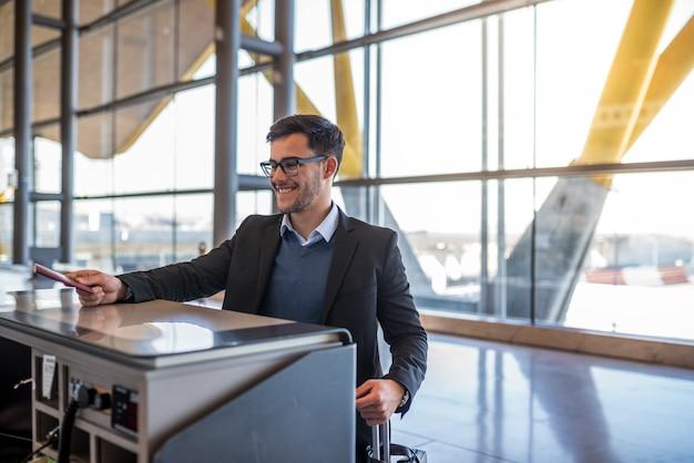 Séduisante jeune homme s'enregistrer à l'aéroport avec son passeport