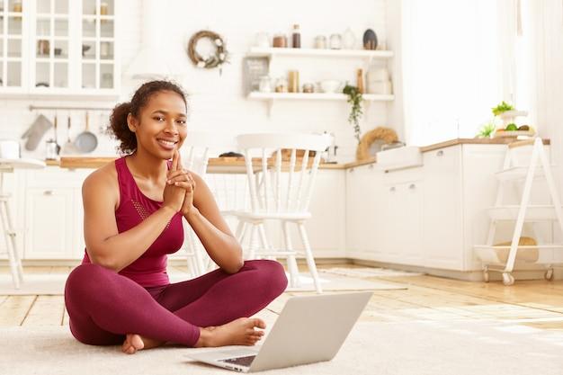 Séduisante jeune instructeur de fitness féminin à la peau sombre travaillant à distance sur un ordinateur portable, assis sur le sol dans des vêtements de sport élégants, écrivant un article sur un mode de vie sain technologie moderne et concept sportif