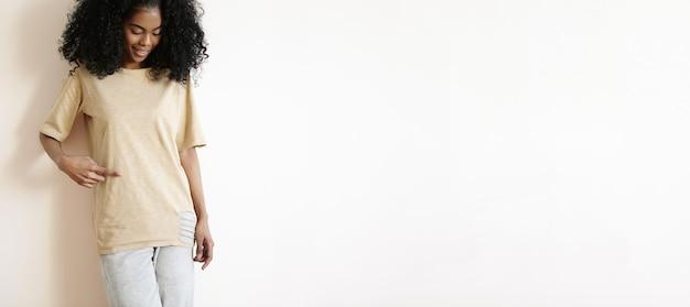 Séduisante jeune mannequin africaine avec une coupe de cheveux bouclée élégante habillée en souriant gaiement, montrant son t-shirt avec le doigt.