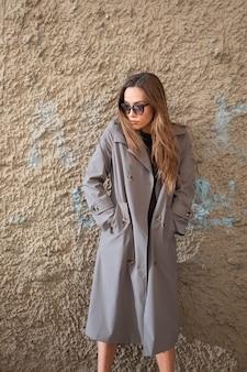 Séduisante jeune mannequin asiatique en trench-coat gris debout près du mur à l'extérieur