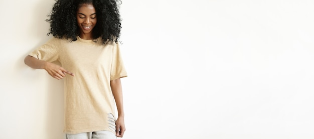 Séduisante jeune mannequin femme africaine portant un t-shirt décontracté, souriant et montrant son t-shirt blanc