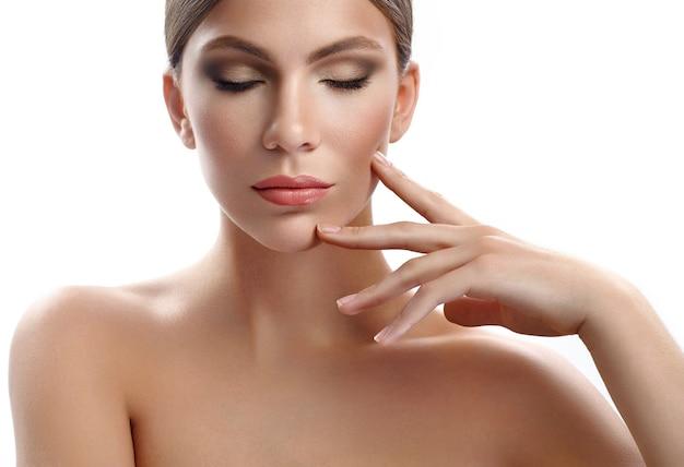 Séduisante jeune mannequin touchant son visage sensuellement