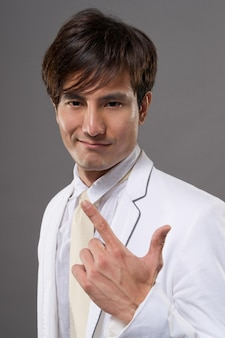 Séduisante jeune mec asiatique en costume blanc, portrait agrandi sur fond gris studio.