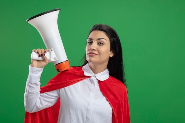 Séduisante jeune superwoman tenant haut-parleur sur place et demi-cambré son sourcil regardant avant isolé sur mur vert