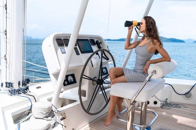 Séduisante et magnifique brune assise et conduisant sur un yacht moderne et tenant des jumelles