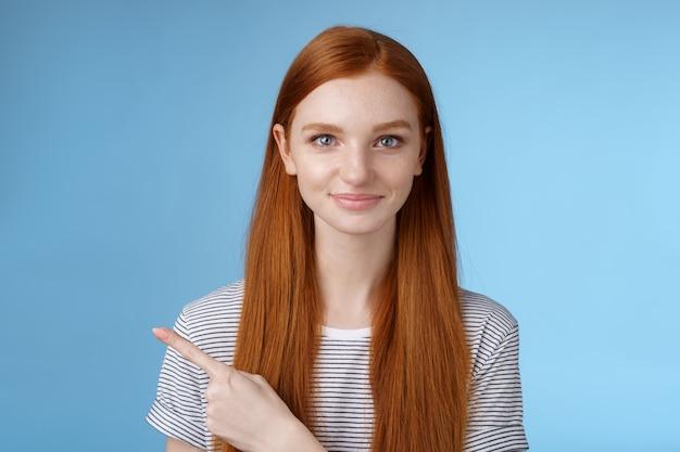 Séduisante petite amie rousse belle et modeste agissant mature amicale souriante pointant l'index gauche donnant la direction montrer comment salle de bain debout fond bleu joyeux sourire aimable