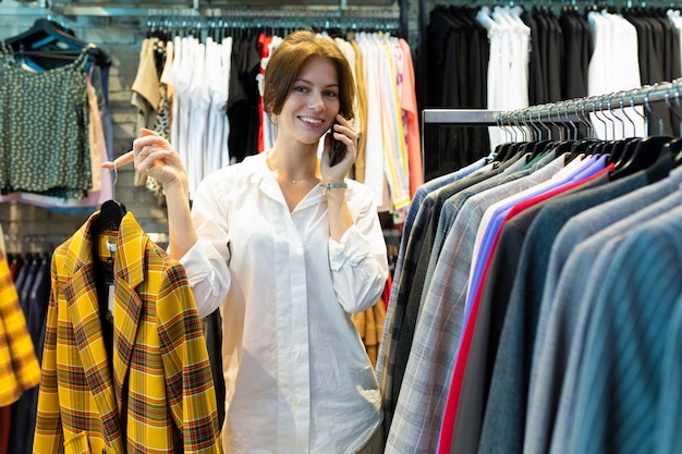 Séduisante vendeuse parle sur phote avec veste dans ses mains.