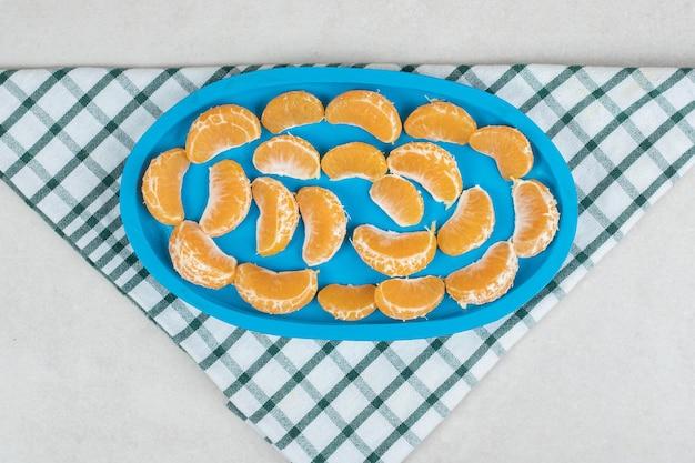 Segments de mandarine juteuse sur plaque bleue
