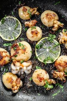 Seiches grillées au citron vert et aux épices dans une poêle. vue de dessus