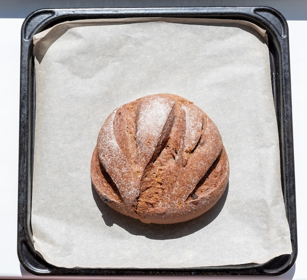 Seigle fait maison fraîchement cuit avec du pain aux raisins secs sur du papier sulfurisé sur une casserole, vue du dessus.