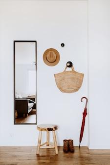 Séjour avec miroir, tabouret, chapeau, sac de paille, parapluie et chaussures.
