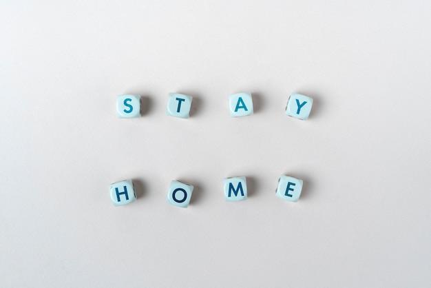 Un séjour en sécurité à la maison pendant les cubes de dés de quarantaine avec un concept simple de texte