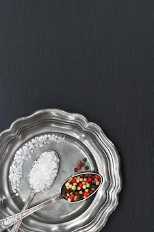 Sel au poivre mélangé dans des cuillères vintage sur une vieille plaque de métal avec une serviette en lin