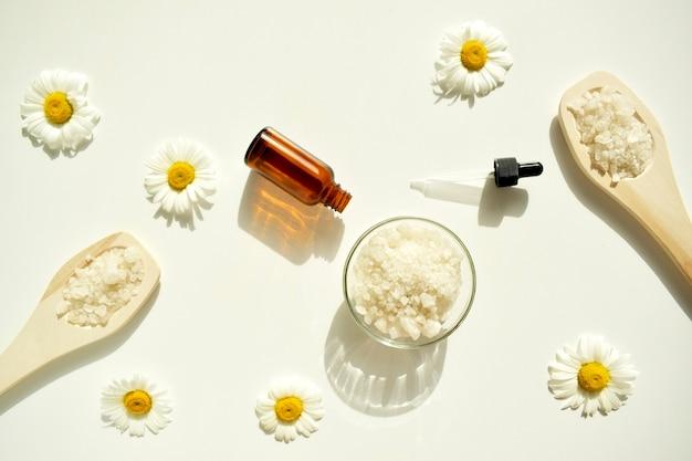 Sel de bain et bocal en verre avec fleurs et pétales de roses, sur fond beige naturel. la vue du haut.