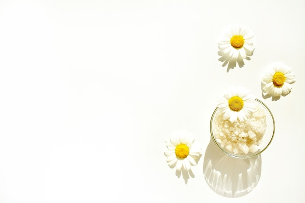 Sel de bain dans un bocal en verre avec des fleurs de camomille sur fond blanc. vue de dessus. copiez l'espace. .