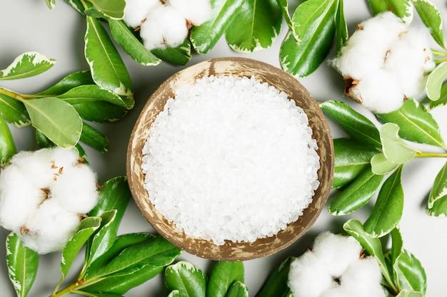 Sel de bain dans un bol de noix de coco, coton et feuilles vertes sur fond gris. concept de spa et de beauté. vue de dessus, pose à plat.