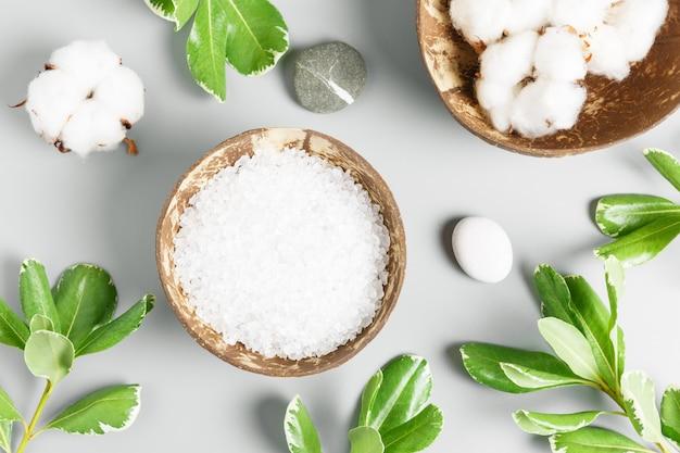 Sel de bain dans un bol de noix de coco, coton et feuilles vertes sur fond gris. concept de spa et de beauté.