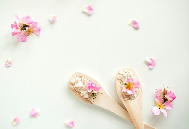 Sel de bain dans des cuillères en bois avec des fleurs et des pétales de rose, sur fond blanc. vue de dessus.