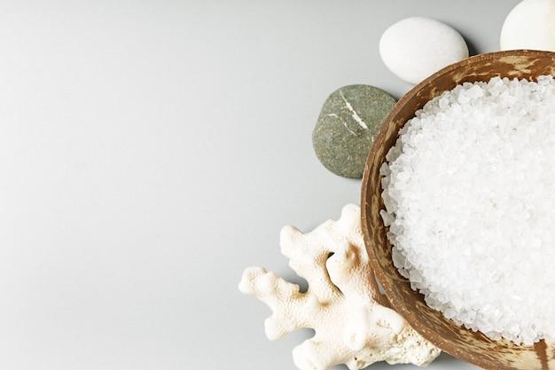 Sel de bain de mer blanc dans un bol de noix de coco, corail et pierres sur fond gris. concept de spa et de relaxation. copie espace