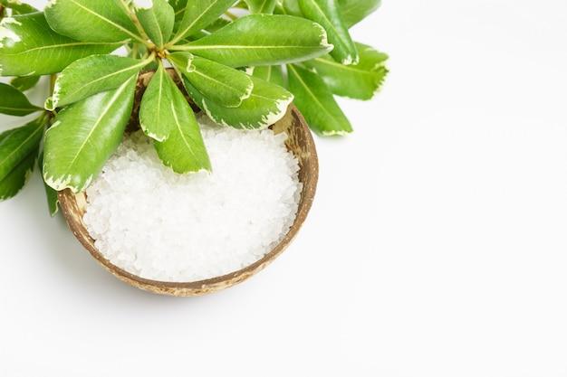 Sel de bain de mer blanc dans un bol de noix de coco et feuilles vertes sur une surface blanche. concept de spa et de relaxation. copie espace