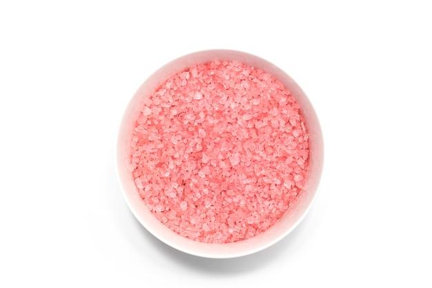 Sel de bain rose dans un bol sur une surface blanche. vue de dessus. concept de spa.