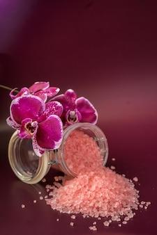 Sel de bain rose avec fleur d'orchidée sur fond vineux. photo de haute qualité