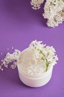Sel de mer blanc dans un pot en plastique et fleurs lilas blanches sur fond lilas concept cosmétique de soins corporels naturels