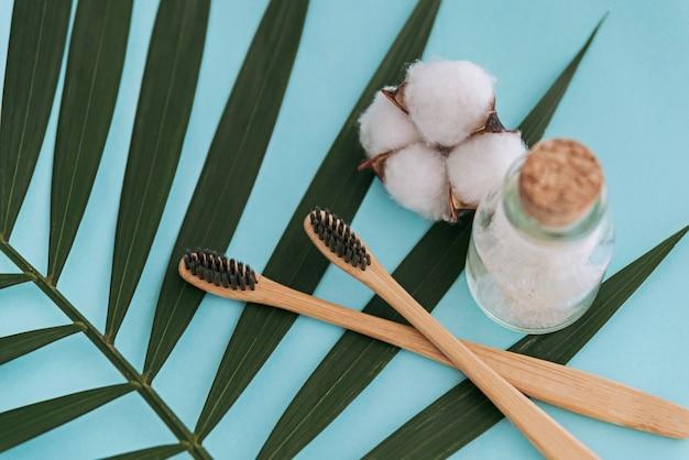 Sel de mer en bouteille en verre, brosses à dents naturelles et fleur de coton sur feuille de palmier bleu