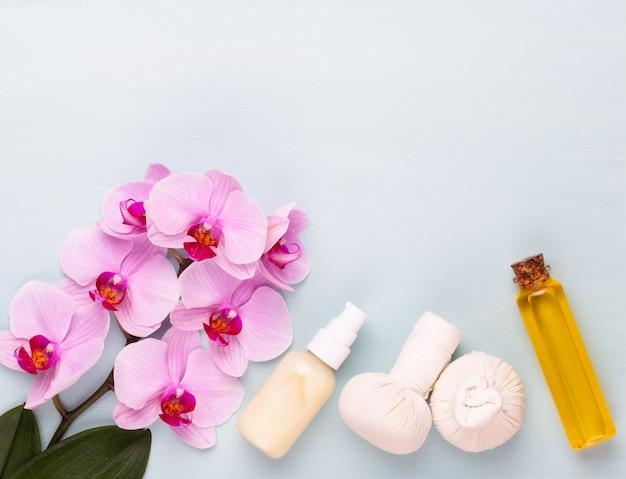 Sel de mer, huile d'aromathérapie en bouteilles et orchidée sur fond en bois vintage.