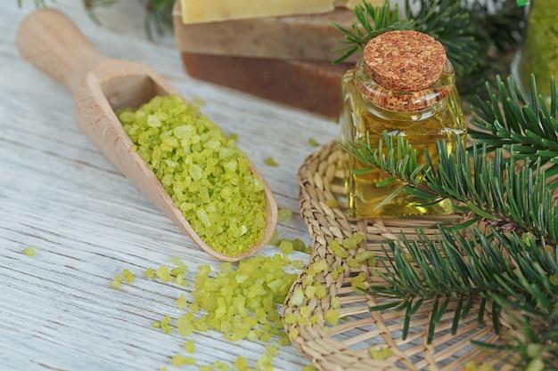 Sel de mer naturel et savon artisanal avec branche de pin sur bois blanc.