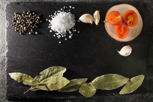 Sel de mer poivre tomates cerises et feuille de laurier sur fond de pierre ardoise rustique noir