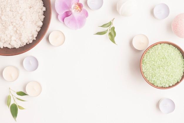 Sel pour bain aromatique dans un plat en argile orné de bougies et fleur d'orchidée sur fond blanc