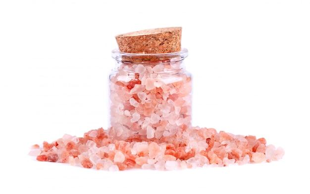 Sel rose de l'himalaya en bocal en verre, isolé sur blanc
