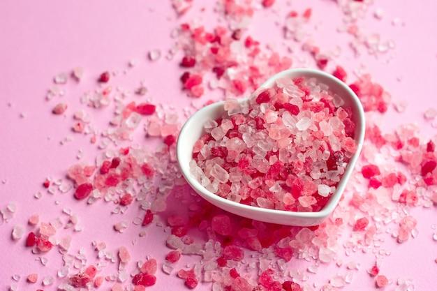 Sel rose de l'himalaya sur fond de papier rose dans une soucoupe en forme de coeur