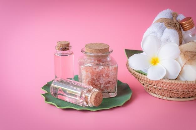 Sel spa, savon liquide au lait et à la rose, serviette blanche, fleurs posées sur des feuilles vertes