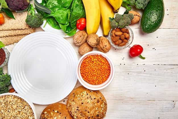 Sélection d'aliments riches en fibres sur fond de bois blanc autour d'une assiette vide
