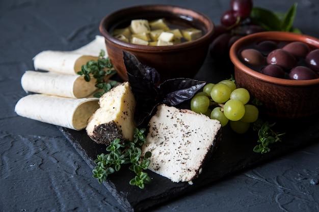 Sélection d'apéritif au fromage. variété de fromage, pain, baguette, raisins, olives