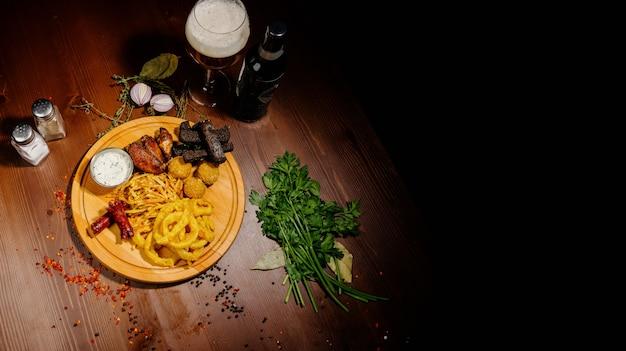 Sélection de bières et snacks. chips, poisson, saucisses à la bière sur la table. vue de dessus