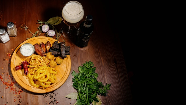 Sélection de bières et snacks. chips, poisson, saucisses à la bière sur la table