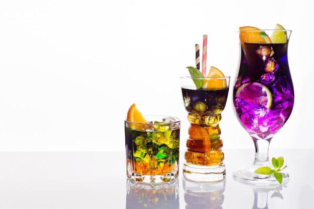 Sélection de boissons festives colorées, de boissons alcoolisées et de cocktails dans des verres élégants sur blanc