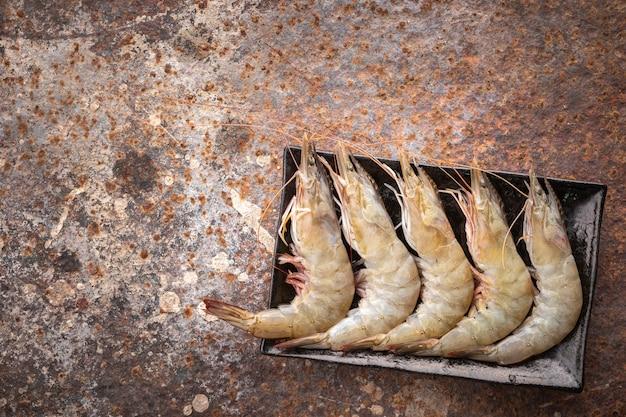 Sélection de crevettes blanches du pacifique crues fraîches dans une plaque en céramique rectangulaire noire sur fond de texture rouillée avec espace de copie pour le texte, vue de dessus, crevettes à pattes blanches