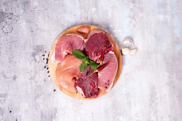 Sélection de différentes viandes crues à l'ail sur une planche de bois. protéines maigres.