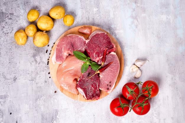 Sélection de différentes viandes crues avec des légumes à une planche de bois. protéines maigres.