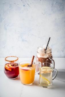 Sélection de diverses boissons traditionnelles d'automne: chocolat chaud à la guimauve, thé au citron et au gingembre, sangria épicée à la citrouille blanche, vin chaud. sur une table en marbre blanc, copie espace, mise au point sélective