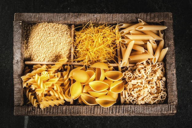 Sélection de diverses pâtes italiennes crues avec des feuilles de basilic et tomate cerise, dans une vieille boîte en bois sur une table en pierre sombre, copyspace vue de dessus