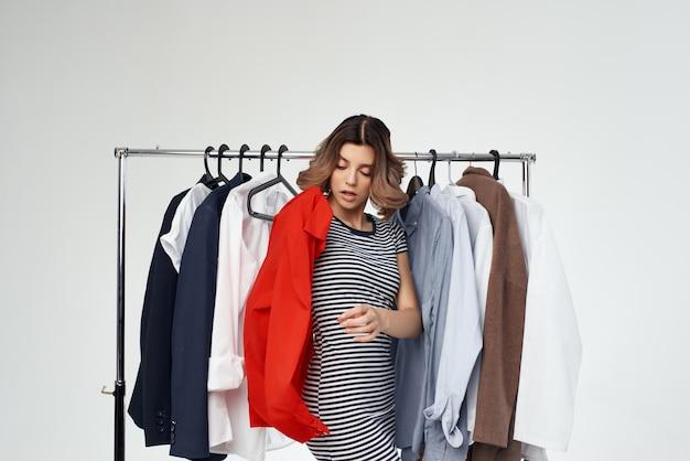 Sélection émotive de femme de vêtements près du fond clair de garde-robe