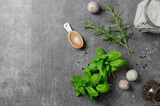 Sélection d'épices herbes et légumes verts, ingrédients pour cuisiner sur fond sombre.