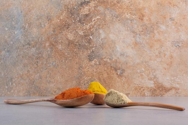 Sélection d'épices indiennes dans des cuillères en bois.